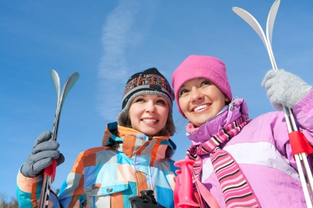 Portrait of two pretty girls with mount  skis against blue sky photo