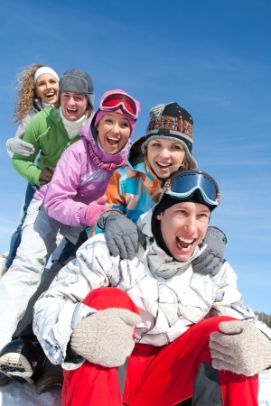 Group of  teenagers slide downhill in wintertime photo