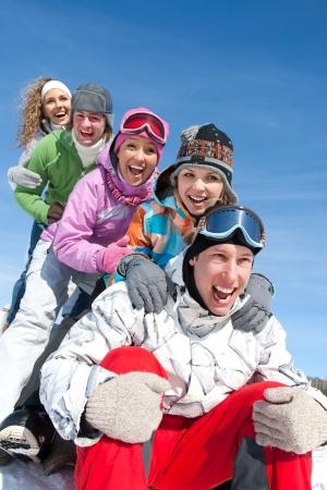 Gruppo di adolescenti in discesa slitta in inverno