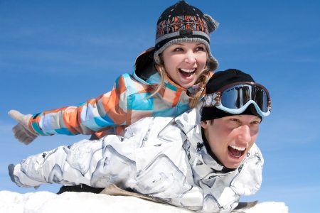 Young couple slide downhill in wintertime photo