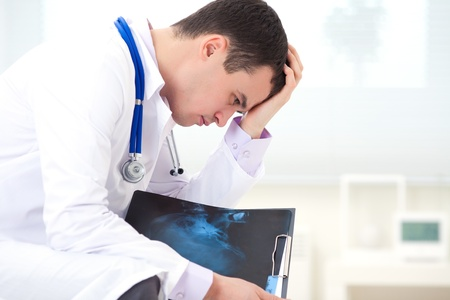 diagnosing: male doctor sitting and experiencing failure with X-ray snapshot of a patient