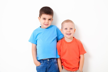 2 5: Two little boys  poses at white wall