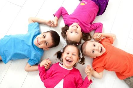 niños felices: Cuatro niños están en el piso junto Vista superior