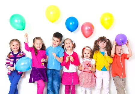 children celebration: Big group of happy children with balloons at white wall Stock Photo