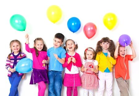Grote groep van gelukkige kinderen met ballonnen op witte muur