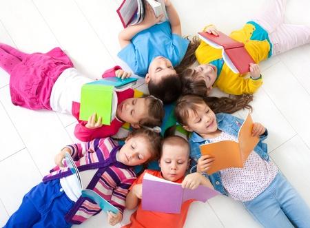 bambini che leggono: Gruppo di bambini godendo lettura insieme Archivio Fotografico