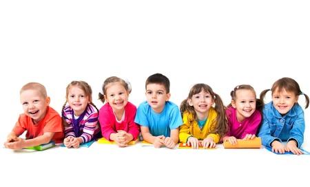 Groep van zeven kinderen liggen op de vloer met copybooks samen