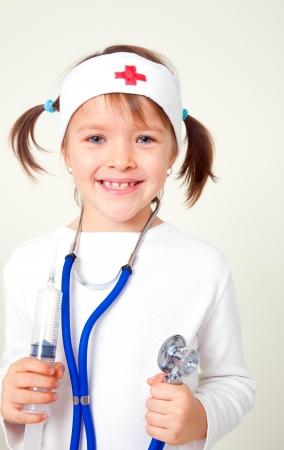 krankenschwester spritze: Portrait eines kleinen h�bschen M�dchen putzt sich als Arzt