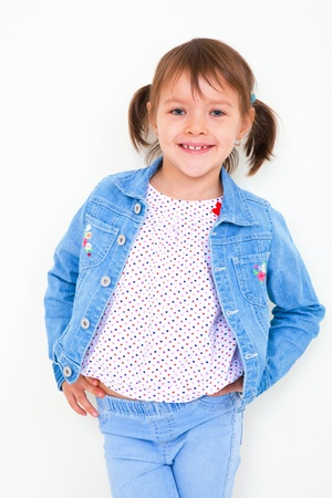 6 years: 6 years old girl in denim suit poses with white wall Stock Photo