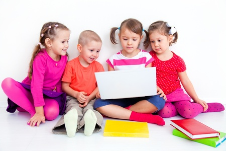 offspring: Group of four children working on laptop together  Stock Photo