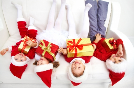 xmas baby: Group of four children in Christmas hat on sofa head over heels