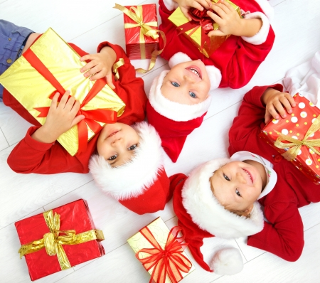 Group of three children in Christmas hat with presents on floor  Stock Photo