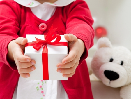 only 1 girl: Hands of  little girl with Christmas present. unrecognizable Stock Photo