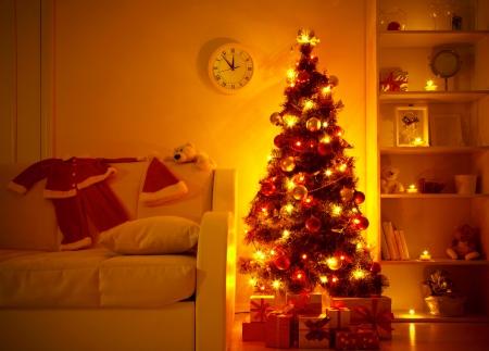 velas de navidad: iluminado �rbol de Navidad con regalos debajo en el sal�n de Foto de archivo