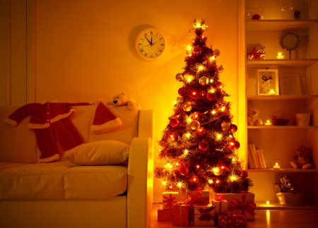 christmas toy:  lighted Christmas tree with presents underneath in living room Stock Photo