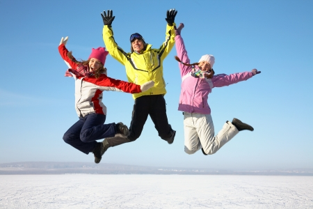 actividades recreativas: tres amigos alegremente saltar en el cielo sobre acumulaciones de nieve en el invierno Foto de archivo