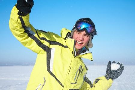 hombres gays: Chico guapo joven feliz jugando en la nieve en la estación de invierno