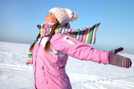Young beautiful girl happy winter day on the background of snowy landscape photo