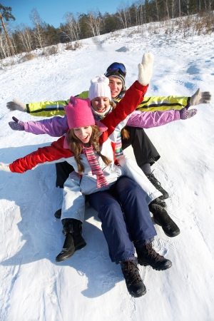 skiers: Group of  teenagers slide downhill in wintertime Stock Photo