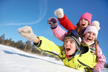 wintertide: Group of  teenagers slide downhill in wintertime Stock Photo