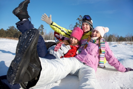 group of young friends tumbles in the snow on a winter vacation photo