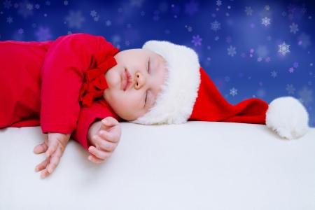 Leuke baby in de hoed slapen in de kerstnacht Stockfoto