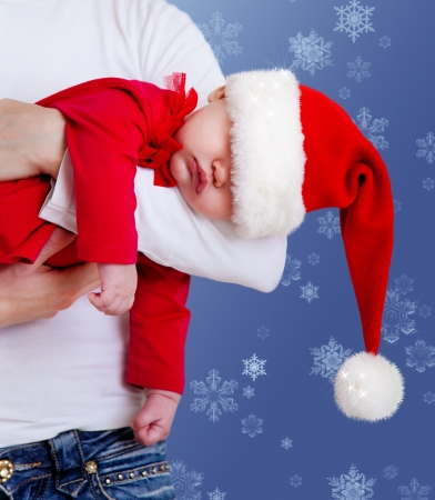 Portrait of Christmas baby is sleeping on mother�s hands photo