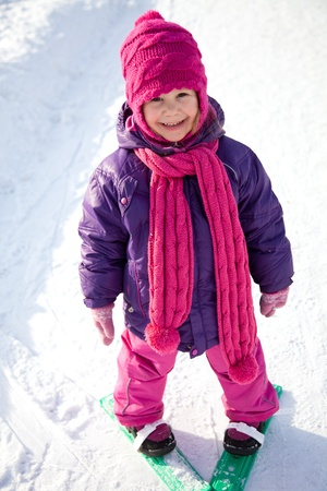 cute little girl is skiing in winter park photo
