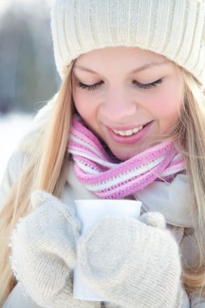 Portrait of blond young woman with hot drink in winter photo