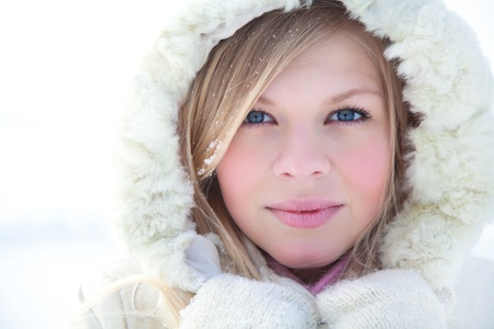 Portrait of blond young woman in fur coat at winter background photo