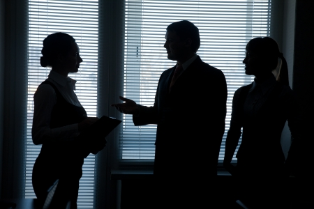 Silhouettes of business team talking on the background of the window in the office  photo