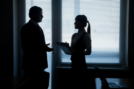 unrecognizable people: silhouettes of business partners talking against the window in the office