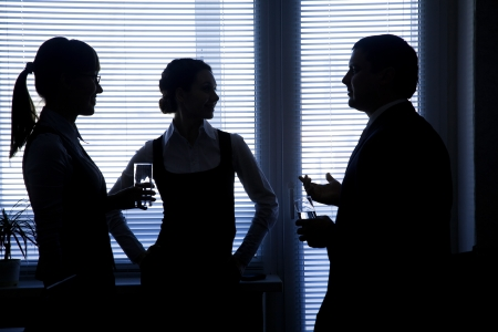 blind people: silhouettes of business partners discuss against the window in the office Stock Photo