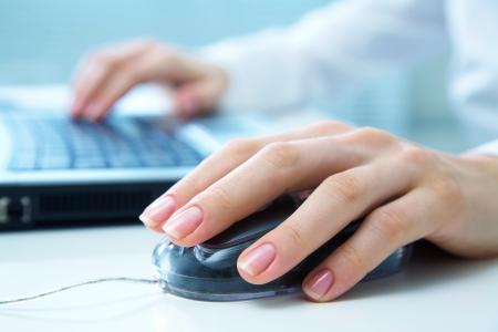 raton: Detalle de las manos de una mujer usando una computadora en fondo de la oficina