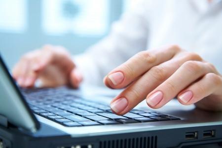 Mani umane lavorando su computer portatile su sfondo ufficio