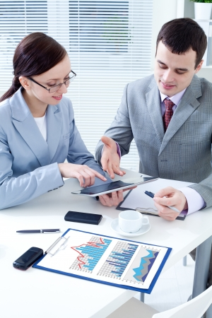 financial leadership: Business colleagues working together and using a digital tablet