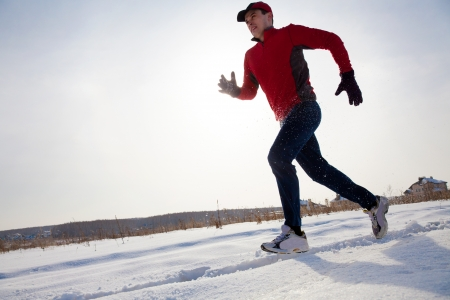 Athletic  man running in winter day on snow road photo