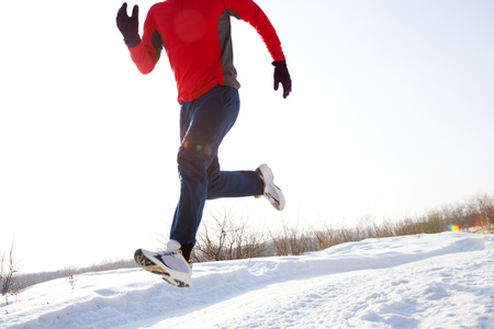 Athletic  man running in winter day  unrecognizable photo