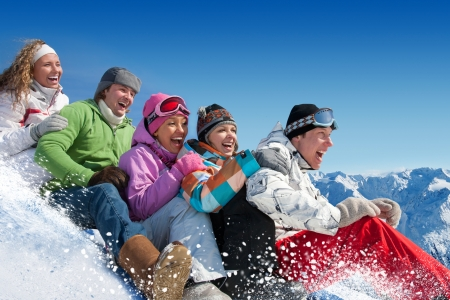 Group of  teenagers slide downhill in winter resort photo