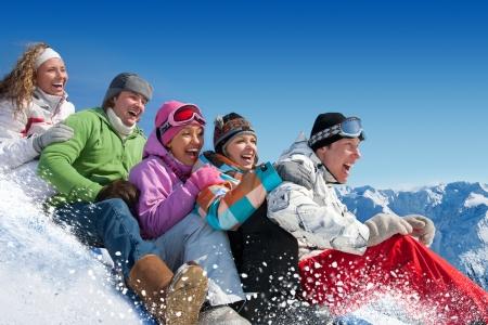 Gruppe von Teenagern Rutsche bergab Wintersportort