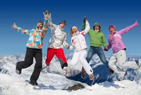 Group of  teenagers jumping together in winter resort in Alps photo