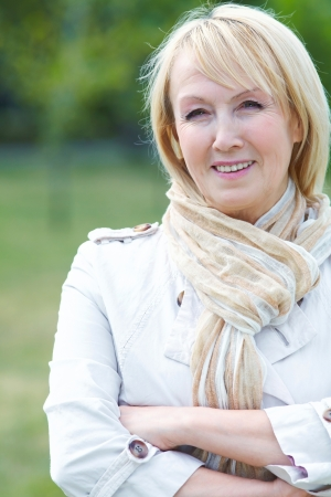 blonde haired: Portrait of happy senior woman in park Stock Photo