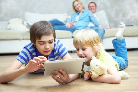 Two children playing with laptop on floor.  Parents sitting on sofa. Selective focus to children. photo