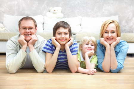family room: Portrait of family lying on floor living room and smiling to camera Stock Photo