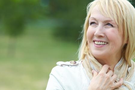 woman scarf: Portrait of happy senior woman in park Stock Photo