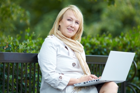 Mature woman sitting on  park bench with  laptop Stock Photo - 17272177