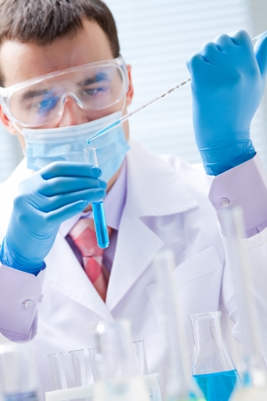 Investigator checking test tubes  Man wears protective goggles Stock Photo - 17510195