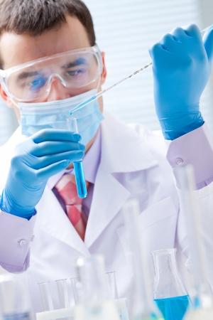 biochemist: Investigator checking test tubes  Man wears protective goggles