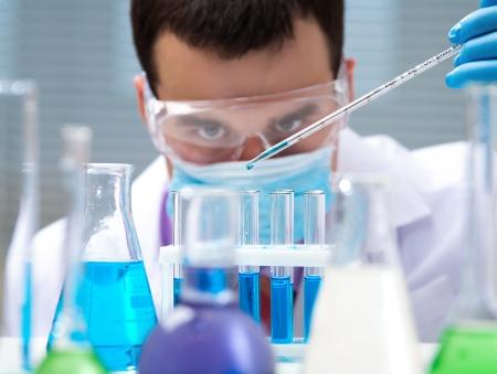 beaker: Investigador prueba de comprobación de tubos hombre lleva gafas protectoras Foto de archivo