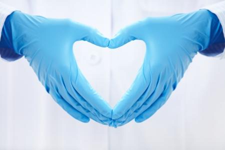 personas ayudando: manos humanas plegado en forma de coraz�n Foto de archivo